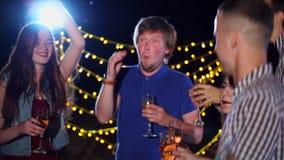Los amigos jovenes con champán en sus manos bailan activamente a los discos en la noche almacen de video