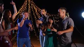 Los amigos jovenes con los vidrios de alcohol a disposición bailan activamente en un disco de la playa almacen de video