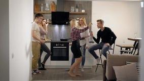 Los amigos jovenes están descansando sobre cocina en el apartamento, están bailando y están entreteniendo en un partido casero en almacen de video