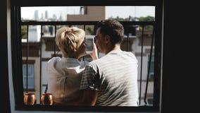Los amigos jovenes felices se sientan juntos en un pequeño balcón de Nueva York, visión desde la ventana del apartamento, usando  almacen de video