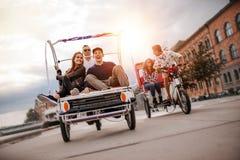 Los amigos jovenes que van en el triciclo montan a través de la ciudad Fotografía de archivo libre de regalías