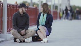 Los amigos jovenes se sientan en valises y hablan en el puente almacen de metraje de vídeo