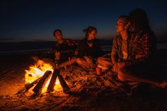 Los amigos jovenes tienen comida campestre con la hoguera en la playa fotografía de archivo