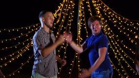 Los amigos jovenes y enérgicos bailan y cantan afuera en el disco en la noche almacen de video
