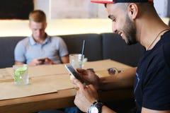 Los amigos masculinos en charla del café discuten con la tableta del teléfono de la tecnología Foto de archivo libre de regalías