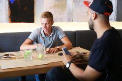 Los amigos masculinos en charla del café discuten con la tableta del teléfono de la tecnología Imagenes de archivo