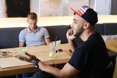 Los amigos masculinos en charla del café discuten con la tableta del teléfono de la tecnología Imágenes de archivo libres de regalías