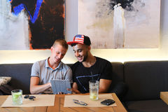 Los amigos masculinos en charla del café discuten con la tableta del teléfono de la tecnología Foto de archivo