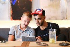 Los amigos masculinos en charla del café discuten con la tableta del teléfono de la tecnología Fotografía de archivo