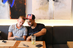 Los amigos masculinos en charla del café discuten con la tableta del teléfono de la tecnología Fotografía de archivo libre de regalías