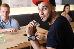 Los amigos masculinos en charla del café discuten con la tableta del teléfono de la tecnología Imagen de archivo libre de regalías