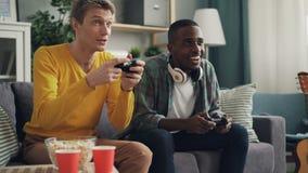 Los amigos masculinos están disfrutando del videojuego que juega juntas en casa sostener las palancas de mando e intentar tener é metrajes