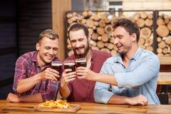 Los amigos masculinos hermosos están gozando de la cerveza dorada en pub Fotografía de archivo