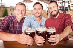 Los amigos masculinos jovenes atractivos están descansando en barra Foto de archivo