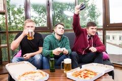 Los amigos masculinos que juegan los videojuegos, la cerveza de la bebida y se divierten en casa Fotografía de archivo