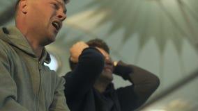 Los amigos masculinos que miraban el juego del deporte en el estadio, se desesperaron de la derrota, casi grito almacen de video