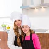 Los amigos menores del cocinero de las muchachas del niño abrazan juntos en cocinar la escuela imagenes de archivo