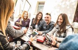 Los amigos milenarios agrupan divertirse usando el teléfono elegante móvil - Y fotos de archivo libres de regalías