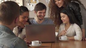 Los amigos miran algo en el ordenador portátil en el café foto de archivo