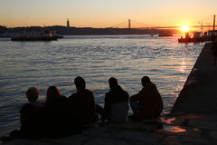 Los amigos miran la puesta del sol Fotografía de archivo