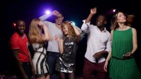 Los amigos mono-étnicos jovenes que bailan en el club y hacen el selfie metrajes