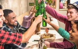 Los amigos multirraciales agrupan la consumición y tostar de la cerveza en el restaurante imagen de archivo libre de regalías