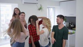 Los amigos multirraciales están bailando y divertirse en cocina, muchachos y muchachas está engañando alrededor en un partido  metrajes