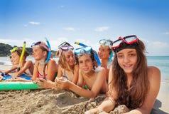 Los amigos ponen en la playa de la arena cerca del mar Imagen de archivo libre de regalías