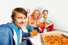 Los amigos positivos sostienen los vidrios y los alistan para la pizza Imagenes de archivo