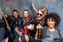 Los amigos que beben la cerveza después de ensayan en estudio Imagen de archivo