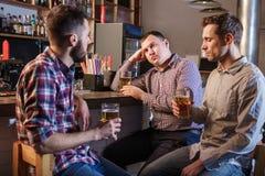 Los amigos que beben la cerveza en el contador en pub Fotografía de archivo libre de regalías