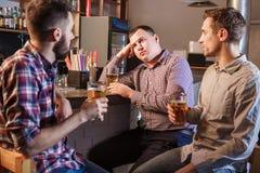Los amigos que beben la cerveza en el contador en pub Imagenes de archivo