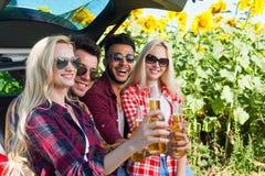 Los amigos que beben la cerveza que tuesta tintineo embotellan sentarse en campo al aire libre del tronco de coche imagen de archivo
