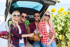 Los amigos que beben la cerveza que tuesta tintineo embotellan sentarse en campo al aire libre del tronco de coche foto de archivo