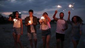 Los amigos que caminan, bailando y divirtiéndose durante partido de la noche en la playa con la bengala de Bengala se encienden e almacen de metraje de vídeo