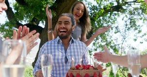 Los amigos que celebran sirven cumpleaños en el restaurante al aire libre almacen de metraje de vídeo