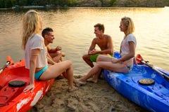 Los amigos que descansan y que hablan mientras que se sientan en kajaks en el río o el lago varan en la puesta del sol Fotos de archivo