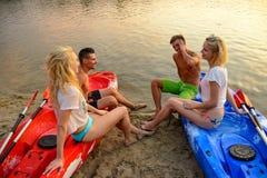 Los amigos que descansan y que hablan mientras que se sientan en kajaks en el río o el lago varan en la puesta del sol Fotografía de archivo libre de regalías