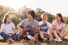 Los amigos que gozan cantando las canciones, pasando el tiempo junto, tienen buen humor, celebratng alguien cumplea?os, pasan ing foto de archivo libre de regalías