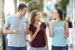 Los amigos que hablan y que comen helado Fotografía de archivo