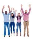 Los amigos que saltan con los brazos aumentados Imágenes de archivo libres de regalías