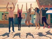 Los amigos que saltan en el día soleado en la calle Imágenes de archivo libres de regalías