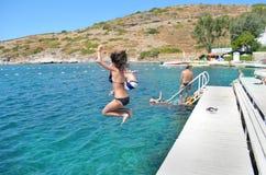 Los amigos que saltan en el mar Foto de archivo libre de regalías