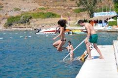 Los amigos que saltan en el mar Fotos de archivo libres de regalías