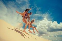 Los amigos que saltan en la duna de arena amarilla Imagen de archivo libre de regalías