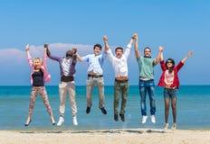 Los amigos que saltan en la playa Imagenes de archivo