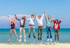 Los amigos que saltan en la playa Fotos de archivo