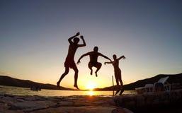 Los amigos que saltan en la puesta del sol en la playa Foto de archivo libre de regalías