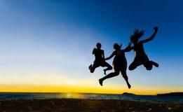 Los amigos que saltan en la silueta de la puesta del sol Foto de archivo