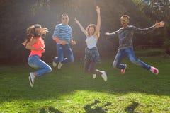 Los amigos que saltan y que se divierten en el día soleado Fotografía de archivo libre de regalías